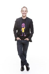 Full-length shot of Andy Griffiths in dark jeans and a blazer over a graphic T-shirt.