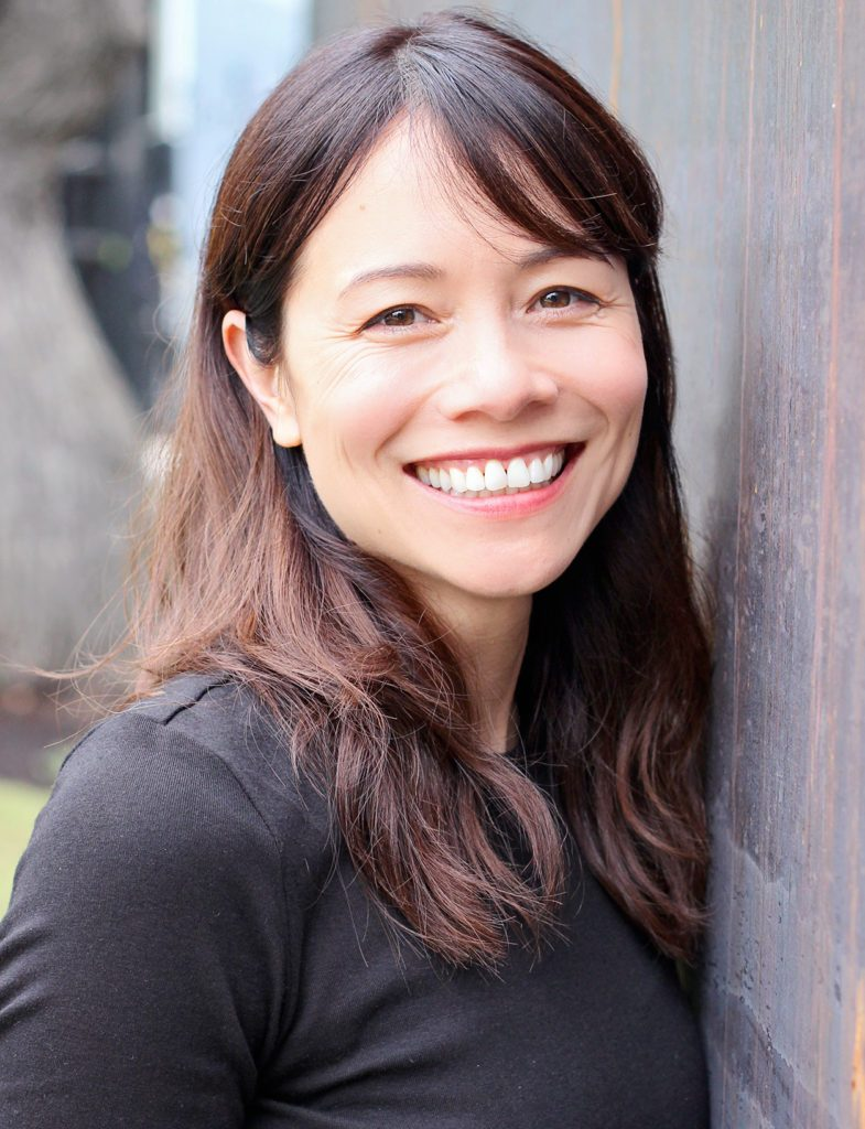 Head shot of Christina Soontornvat smiling in an outdoor environment.