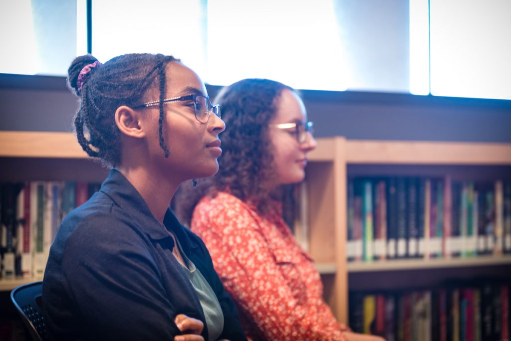 Profile of two ambassadors actively listening at an author event.