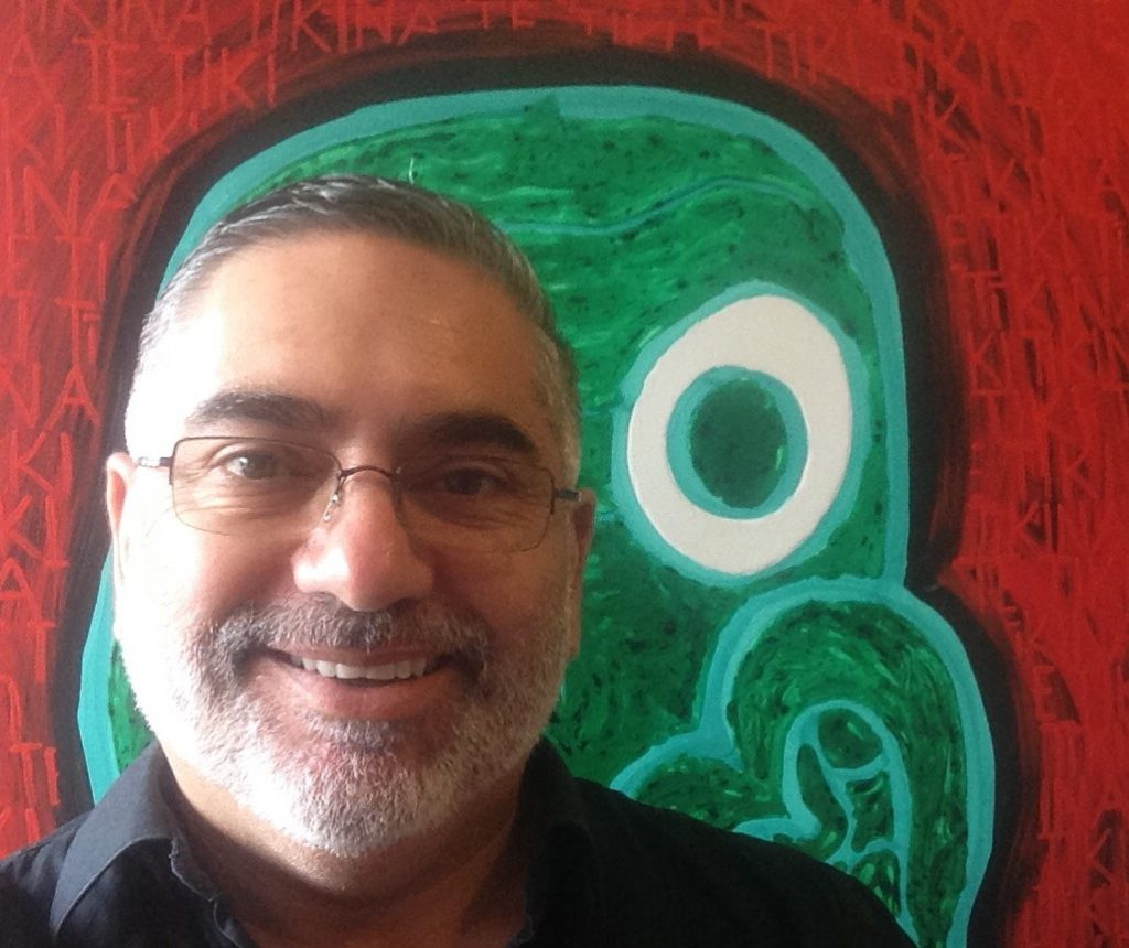 Head shot of Darryn Joseph. Behind him is one of his paintings of bold strokes in green and red.