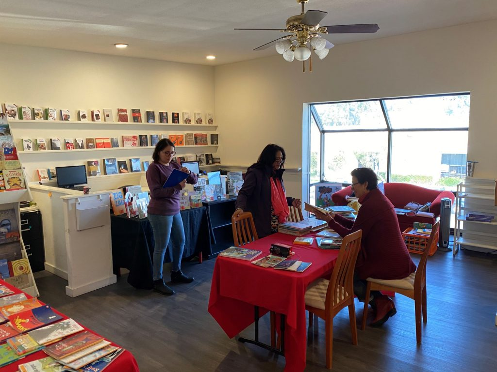 Three people looking a books, which line the room on shelves and tables covered in red or blue tablecloths.
