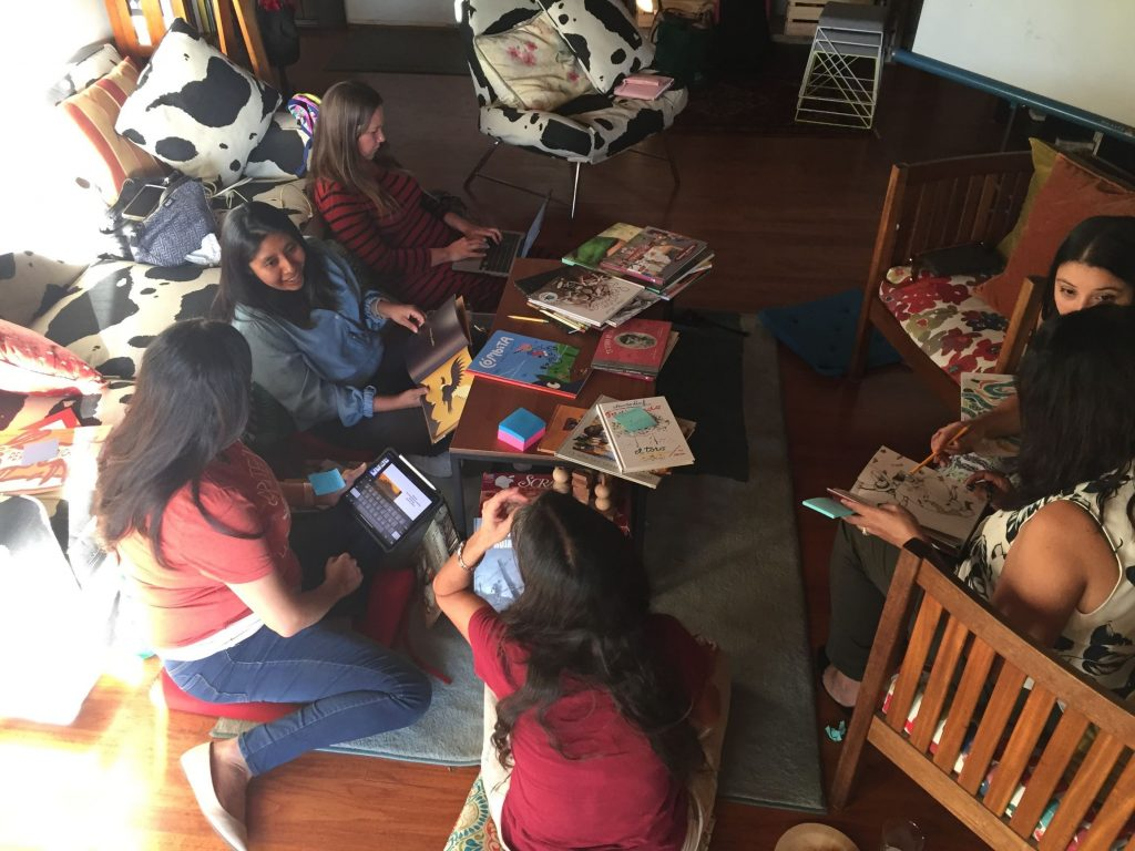 A group of students are seated around a low table covered in picturebooks.