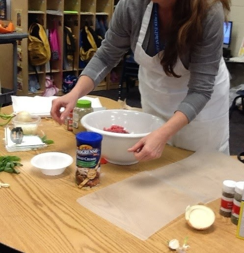 Image of a teacher in a white apron mixing ingredients into a white plastic bowl on a wooden table. There is a sheet of plastic besides the bown and various bottles of spices on the table.