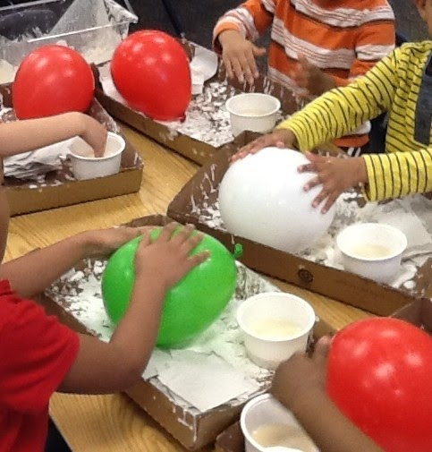Image of a group of four young children rolling balloons in a tray of flour. In the back are two red balloons, while the children closer to the camera ar eusing green (left side) and white (right side).