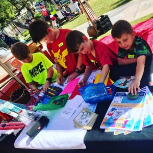 Four boys involved in a hands-on activity under the shade of WOW's tent at Tucson Children's Museum's Love of Literacy Festival