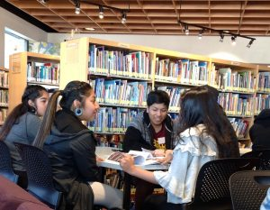 Students from Tohono O'odham High School engage in a lively discussion around a table