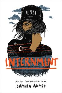 Cover for Internment shows a teen girl with her face obscured wearing a baseball cap with RESIST printed on it, overlaying her shirt is an image of a wall topped with barbed wire