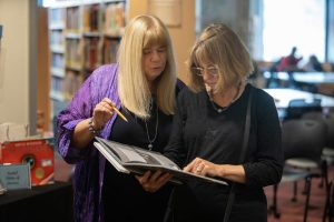 Kathy Short and Gudrun Godare read a visual narrative at exhibit reception