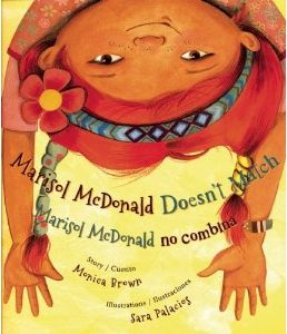 Cover for Marisol McDonald features an upside down girl with red braids and arms hanging down
