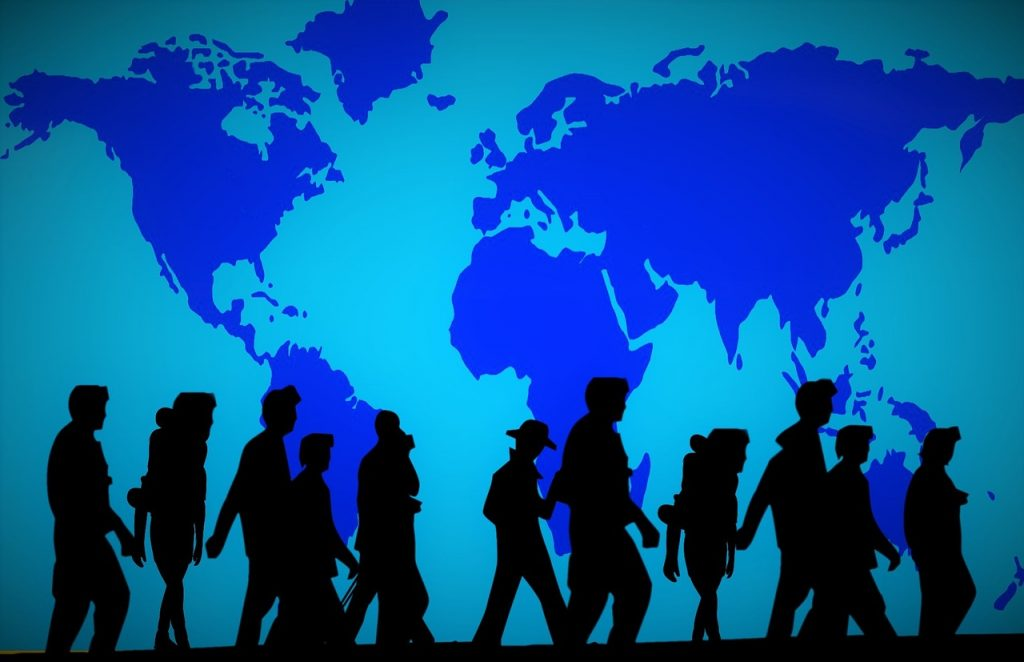 Decorative image of a blue wall featuring a world map with silhouettes of people walking past.