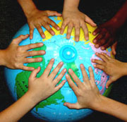 The hands of children with varying skin tones on the northern hemisphere of a globe