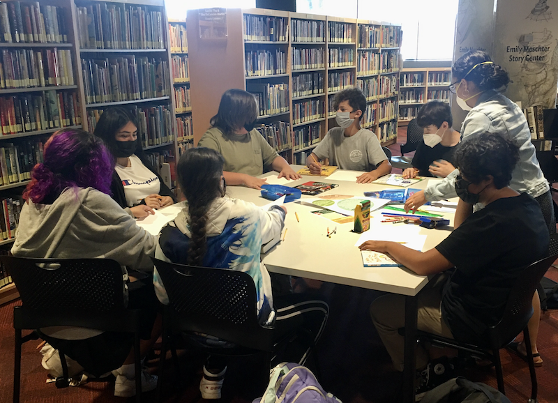 Younger teens sit around a large table creating heart and mind maps using paper, color pencils, crayons, markers and rulers.