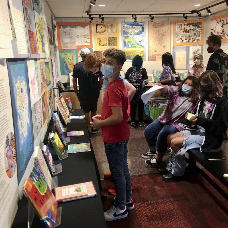 Young teens reading and discussing the books and posters on display.
