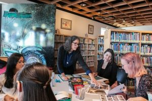 Four women work with exhibit materials around a table. Photo by Vincent Tran of the Daily Wildcat.