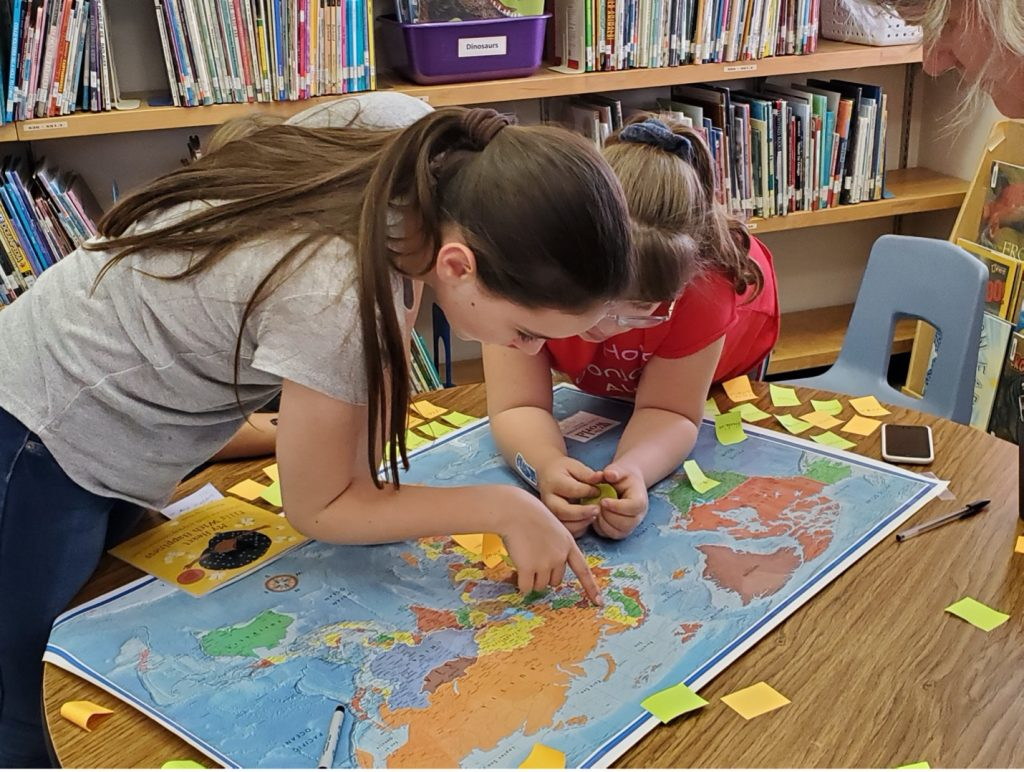 Two girls bend over a table to examine a map. Yellow post-its are scattered on the table. One of the girls points to eastern Europe.