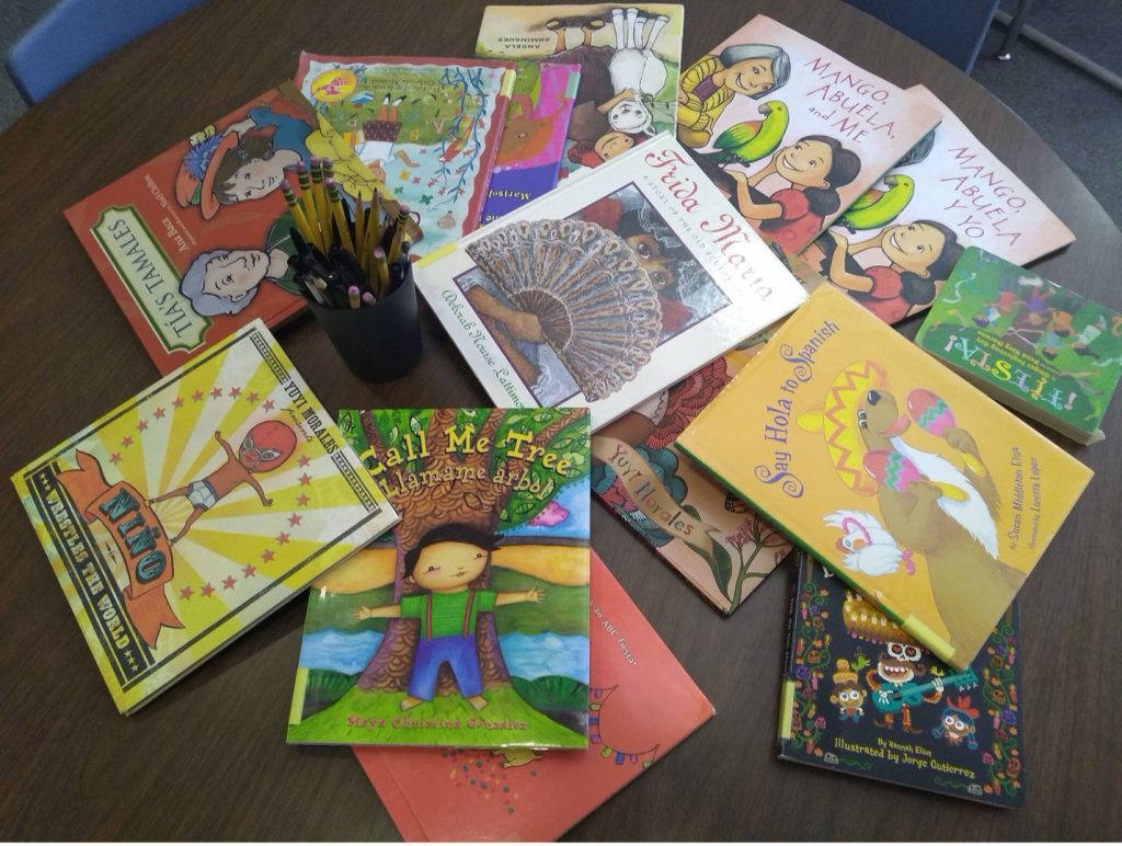 14 picture books are fanned out on a table in a circle by a can of pens and pencils.