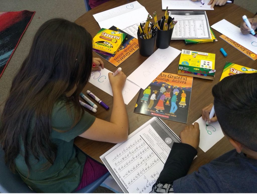 A boy and a girl lean over papers and markers. Copies of the book We Are Grateful are also on the table.