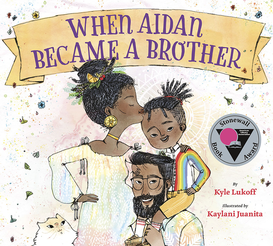 Cover of When Aidan Became a Brother, depicting a black family of a mother, father, and young boy on the father's shoulders while his mother kisses his forehead. They are in front of a white background with confetti in the back, and a small white cat in the lower left corner.