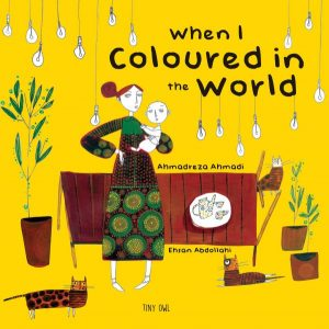 Cover art for When I Coloured in the World is a flattened illustration of a woman holding a baby in front of a dining room table with edison bulbs hanging from the top of the book, two plants and three cats filling the room.