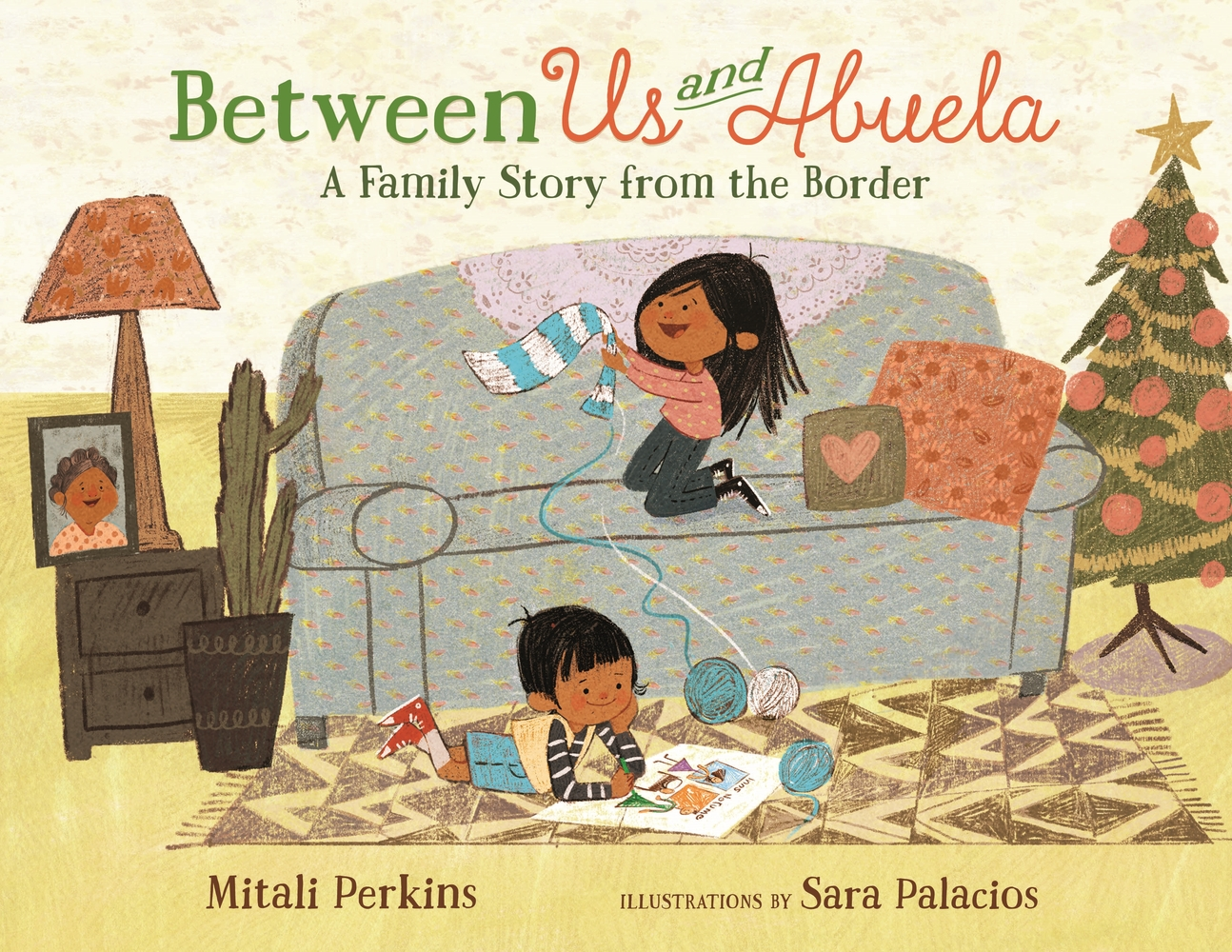 Cover of Between Us and Abuela depicting two children, one on a grey couch making a scarf and the other on a colorful rug, drawing.