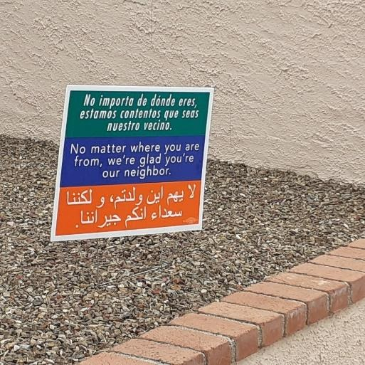 A sign reading No matter where you're from, we're glad you're our neighbor in Spanish, English and Arabic on a green, blue and orange background