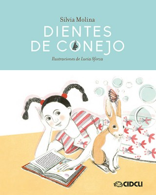 Cover of dientes de conejo depicting a young girl with black braided pigtails laying on the floor besides a bunny, reading a book.