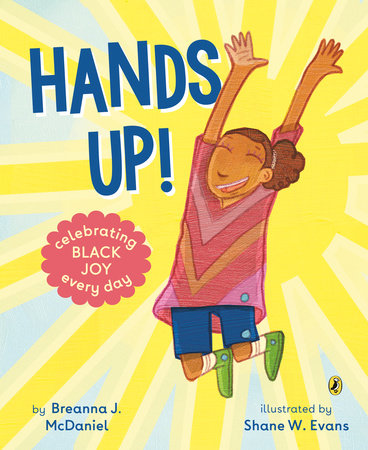 The cover of Hands Up! depicts a young brown girl jumping in the air with her hands up, smiling, in front of a yellow background that resembles the sun.