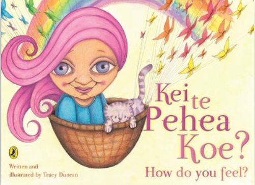 Cover of Kei Te Pehea Koe? with a woman with pink hair and a grey cat in a basket in front of a rainbow