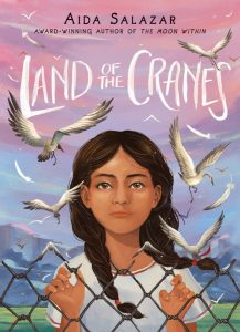 Cover of Land of the Cranes, depicting a young girl with two braided pigtails looking at the viewer with her fingers curled around the gaps in a chain link fence. Small cranes fly around her face and the background in a pink to light blue gradient sky and mountains.